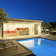 Evening view of the poolside living area - architecture, backyard, cottage, estate, home, house, lighting, property, real estate, residential area, sky, swimming pool, villa, blue, brown