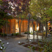 View of private courtyard which features native planting, autumn, backyard, cottage, evening, home, house, landscape, landscape lighting, leaf, lighting, outdoor structure, plant, property, real estate, tree, yard, brown