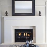 View of the lounge area which features sofas, fireplace, hearth, home appliance, interior design, wood burning stove, white