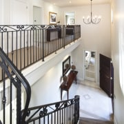 View of stairway which features iron balustrade and baluster, floor, flooring, handrail, hardwood, home, interior design, product, real estate, room, stairs, wood, white