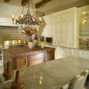 View of a traditional-styled kitchen which features a cabinetry, countertop, cuisine classique, flooring, interior design, kitchen, room, brown, orange