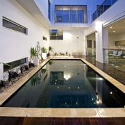 Evening view of the poolside area - Evening apartment, condominium, estate, home, house, interior design, property, real estate, swimming pool, gray
