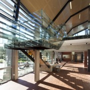 Interior close-up of the large stairway that joins architecture, building, ceiling, daylighting, glass, lobby, structure, brown