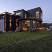 Evening view of this modern home overlooks the cottage, facade, home, house, property, real estate, roof, siding, black, teal