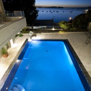 Evening view of the outdoor pool area - leisure, lighting, pool, property, real estate, reflection, sky, swimming pool, water, blue