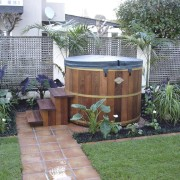 Exterior view of this hot tub & surround backyard, garden, grass, landscaping, outdoor structure, plant, wood, yard, gray, green