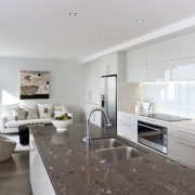 View of kitchen area which features island, granite countertop, cuisine classique, floor, interior design, kitchen, living room, property, real estate, gray, white