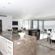 View of kitchen area which features island, granite apartment, countertop, interior design, kitchen, property, real estate, white
