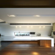 View of kitchen area featuring hardwood flooring, island architecture, ceiling, daylighting, floor, flooring, hardwood, house, interior design, lighting, loft, room, wood, brown, gray