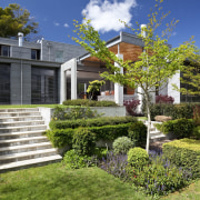 Exterior view of flat roof house which is architecture, backyard, cottage, estate, facade, garden, grass, home, house, landscape, landscaping, lawn, neighbourhood, outdoor structure, plant, property, real estate, residential area, suburb, tree, walkway, yard, brown