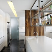 View of a bar style kitchen which features countertop, interior design, kitchen, real estate, white