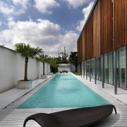 View of the outdoor area which features a architecture, condominium, house, leisure, real estate, reflection, sky, swimming pool, water, gray