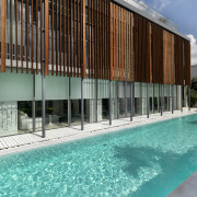 View of the outdoor area which features a architecture, building, condominium, facade, leisure, leisure centre, property, real estate, reflection, swimming pool, water, teal