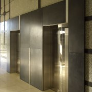 View of brass walls fabricated by Craft Metals door, glass, interior design, lobby, wall, brown
