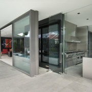 View of the wet kitchen which features stainless architecture, door, glass, house, real estate, gray