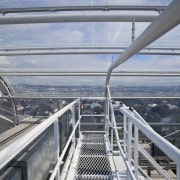 View of the roof of the south stand building, deck, fixed link, sky, skyway, water, gray
