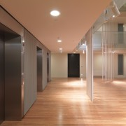 View of the elevators at the Tripych apartments. architecture, ceiling, daylighting, floor, flooring, hardwood, interior design, laminate flooring, lighting, lobby, real estate, wood, wood flooring, brown, orange