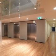 View of the elevators at the Tripych apartments. ceiling, floor, flooring, hardwood, interior design, laminate flooring, lighting, lobby, real estate, wood, wood flooring, orange, brown
