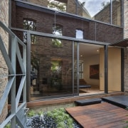 View of a renovated three-story home, built to architecture, backyard, courtyard, facade, home, house, outdoor structure, real estate, residential area, siding, yard, gray, black