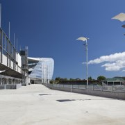 View of concrete pedestrian bridge at Eden Park architecture, boardwalk, building, city, cloud, daytime, fixed link, infrastructure, sky, street light, structure, walkway, blue, white