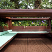 View of timber outdoor seating area with large backyard, bench, deck, furniture, outdoor furniture, outdoor structure, table, wood, red