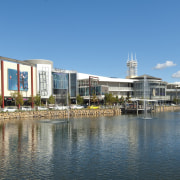 Exterior view of the Robina Town Centre where canal, city, mixed use, real estate, reflection, sky, water, waterway, teal