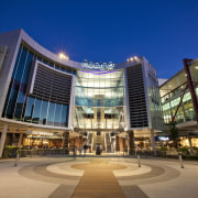 Exterior view of the Robina Town Centre where architecture, building, city, commercial building, condominium, convention center, corporate headquarters, downtown, headquarters, hotel, metropolis, metropolitan area, mixed use, night, plaza, real estate, residential area, shopping mall, sky, blue