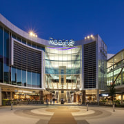 Exterior view of the Robina Town Centre where architecture, building, city, commercial building, condominium, convention center, corporate headquarters, headquarters, hotel, metropolis, metropolitan area, mixed use, plaza, real estate, shopping mall, sky, blue