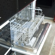 View of kitchen which features integrated Smeg dishwasher black, white