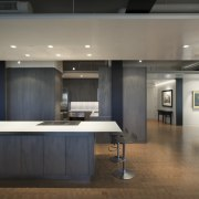 View of an apartment kitchen with dark-toned cabinetry, architecture, ceiling, countertop, floor, flooring, interior design, kitchen, gray, black