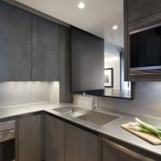 View of an apartment kitchen with dark-toned cabinetry, cabinetry, countertop, interior design, kitchen, real estate, under cabinet lighting, gray, black
