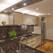 View of a kitchen which features timber floors, cabinetry, ceiling, countertop, floor, interior design, kitchen, under cabinet lighting, brown