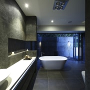 View of dark-toned bathroom with white tub. - architecture, bathroom, ceiling, daylighting, estate, interior design, room, black, gray