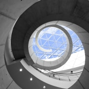 A dramatic spiral concrete staircase is a feature angle, architecture, circle, daylighting, daytime, light, line, product design, sky, spiral, structure, wheel, black, gray