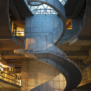 A dramatic spiral concrete staircase is a feature architecture, building, daylighting, landmark, sky, stairs, structure, symmetry, tourist attraction, black, brown