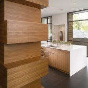 View of sculptural bank of wooden cabinetry, reflecting cabinetry, countertop, floor, flooring, furniture, hardwood, interior design, kitchen, laminate flooring, plywood, wall, wood, wood flooring, wood stain, brown