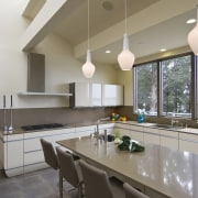 View of neutral-toned kitchen and dining space, featuring architecture, ceiling, countertop, daylighting, floor, house, interior design, kitchen, real estate, table, gray
