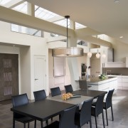 View of neutral-toned kitchen and dining space, featuring ceiling, countertop, dining room, interior design, kitchen, real estate, room, table, gray
