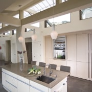 View of neutral-toned kitchen and dining space, featuring cabinetry, ceiling, countertop, cuisine classique, daylighting, interior design, kitchen, gray, brown