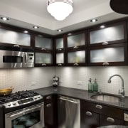 View of kitchen in Art-Deco styled apartment building, cabinetry, ceiling, countertop, cuisine classique, interior design, kitchen, room, under cabinet lighting, white, black, gray