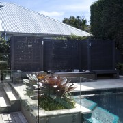 The rear yard of this home has been architecture, daylighting, home, house, reflection, roof, swimming pool, water, black, teal