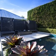 The rear yard of this home has been architecture, flower, home, house, landscape, plant, real estate, reflection, sky, tree, blue