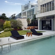 View of pool area at a contemporary home. apartment, backyard, condominium, estate, home, house, leisure, outdoor furniture, property, real estate, residential area, sunlounger, swimming pool, gray