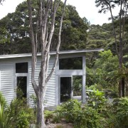 View of contemporary home surrounded by trees. - architecture, cottage, home, house, jungle, plant, property, rainforest, real estate, tree, brown