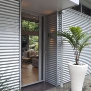 Entrance way of contemporary home surrounded by trees. architecture, courtyard, door, home, house, interior design, porch, real estate, siding, window, window covering, gray