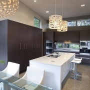 View of contemporary kitchen with decorative lighting features. architecture, ceiling, countertop, interior design, kitchen, table, gray