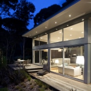Nighttime shot of contemporary home surrounded by trees. architecture, cottage, daylighting, estate, facade, home, house, lighting, property, real estate, residential area, siding, window, black