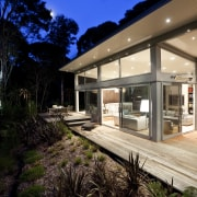 Nighttime shot of contemporary home surrounded by trees. architecture, backyard, estate, home, house, interior design, property, real estate, window, black