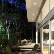 Nighttime shot of contemporary home surrounded by trees. architecture, daylighting, deck, home, house, interior design, outdoor structure, patio, real estate, black, orange