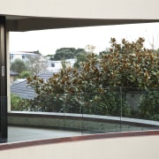 View of home with curved, toughened glass balustrade. architecture, glass, home, house, property, tree, window, white